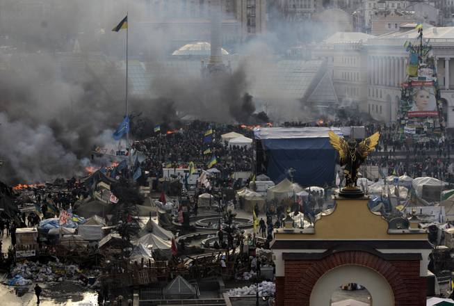 Anti-government protesters clash with riot police in Kiev's Independence Square, the epicenter of the country's current unrest, Kiev, Ukraine, Wednesday, Feb. 19, 2014.