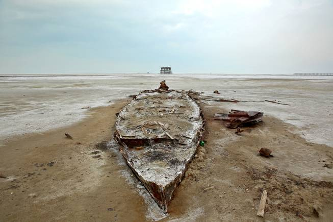 In this Sunday, Feb. 16, 2014 photo, the wreckage of a boat is stuck in the solidified salts and sands at Lake Oroumieh, northwestern Iran.
