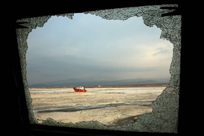 In this Sunday, Feb. 16, 2014 photo, an abandoned boat is seen through the shattered window of an abandoned ship, both stuck in solidified salt at Lake Oroumieh, northwestern Iran.