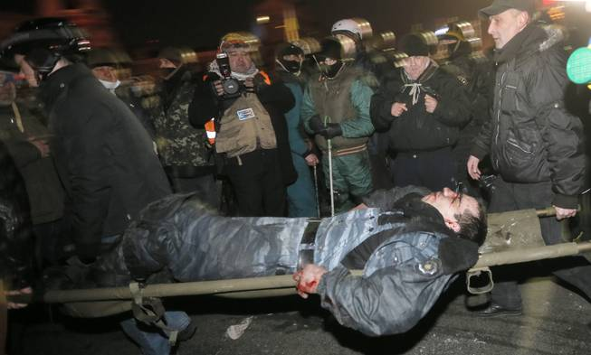 Anti-government protesters carry a wounded policemen during clashes with riot police in Kiev's Independence Square, the epicenter of the country's current unrest,  Kiev, Ukraine, Wednesday, Feb. 19, 2014. Thousands of angry anti-government protesters clashed with police in a new eruption of violence following new maneuvering by Russia and the European Union to gain influence over this former Soviet republic.