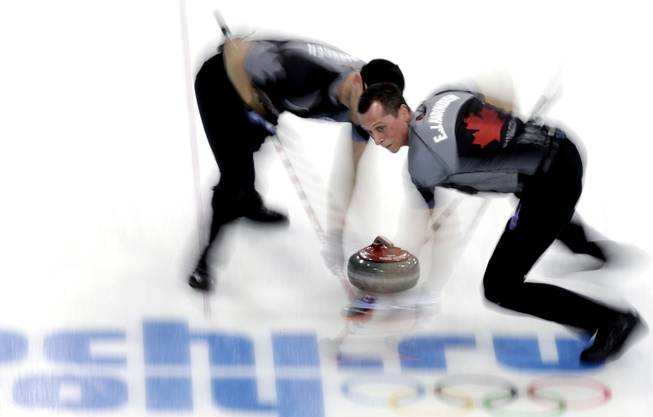 Canada's E.J. Harnden, right, and Ryan Harnden, left, sweep ahead of the rock during the men's curling semifinal game against China at the 2014 Winter Olympics, Wednesday, Feb. 19, 2014, in Sochi, Russia.