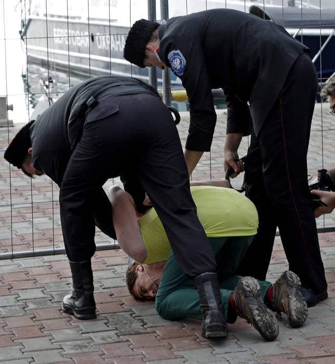 A member of the punk group Pussy Riot is restrained by Cossack militia after the group tried to perform in Sochi, Russia, on Wednesday, Feb. 19, 2014.