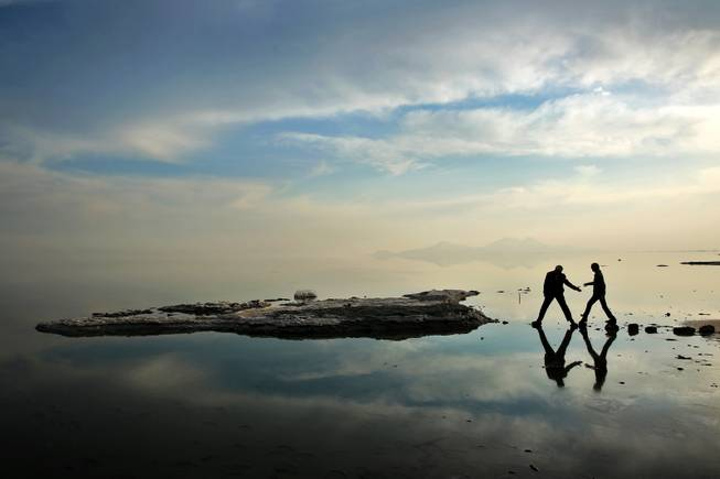 In this Saturday, Feb. 15, 2014 photo,  two men walk toward salt-covered rocks that were once deep underwater at Lake Oroumieh, in northwestern Iran.