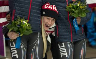 Canada's Kaillie Humphries pokes her head between the silver medallists from the USA after she and Heather Moyse won the gold medal in women's bobsled at the Sochi Winter Olympics in Krasnaya Polyana, Russia, Wednesday, Feb. 19, 2014.