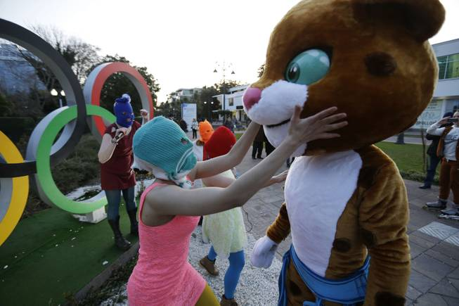Pussy Riot member Nadezhda Tolokonnikova in the aqua balaclava, left, interacts with an Olympic mascot while the group perform next to the Olympic rings in Sochi, Russia, on Wednesday, Feb. 19, 2014.