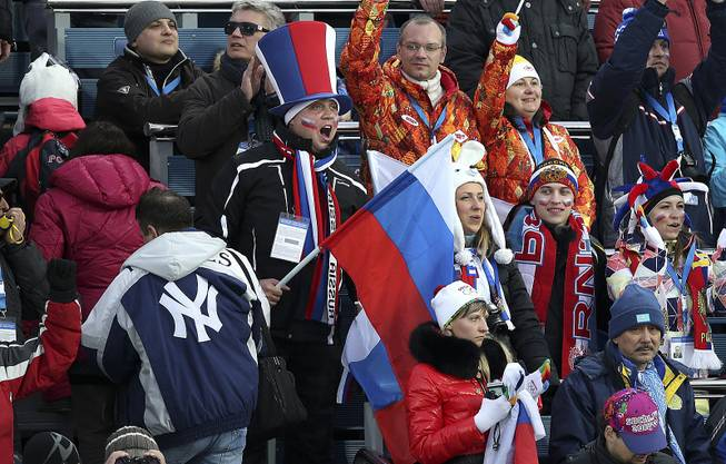 Fans waving a Russian flag cheer during the women's biathlon at the 2014 Winter Olympics in Krasnaya Polyana, Russia, Feb. 9, 2014.