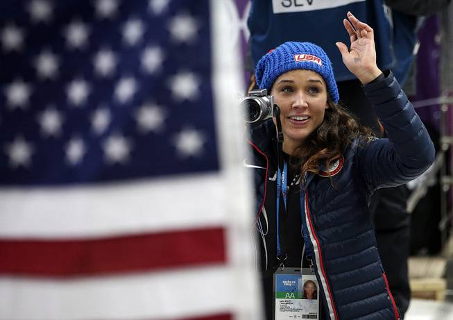American bobsledder Lolo Jones takes pictures of her teammates after they won silver and bronze during the women's bobsled competition at the 2014 Winter Olympics, Wednesday, Feb. 19, 2014, in Krasnaya Polyana, Russia.