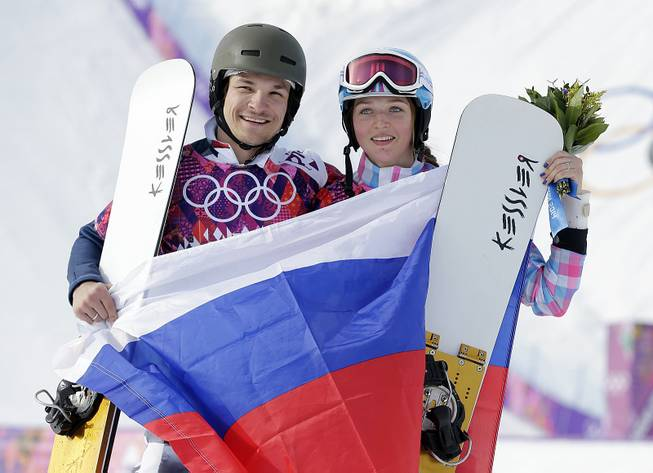 Russia's Vic Wild celebrates, after winning the gold medal in the men's snowboard parallel giant slalom final, with his wife and bronze medalist in the women's snowboard parallel giant slalom final, Russia's Alena Zavarzina, at Rosa Khutor Extreme Park at the 2014 Winter Olympics, Wednesday, Feb. 19, 2014, in Krasnaya Polyana, Russia.