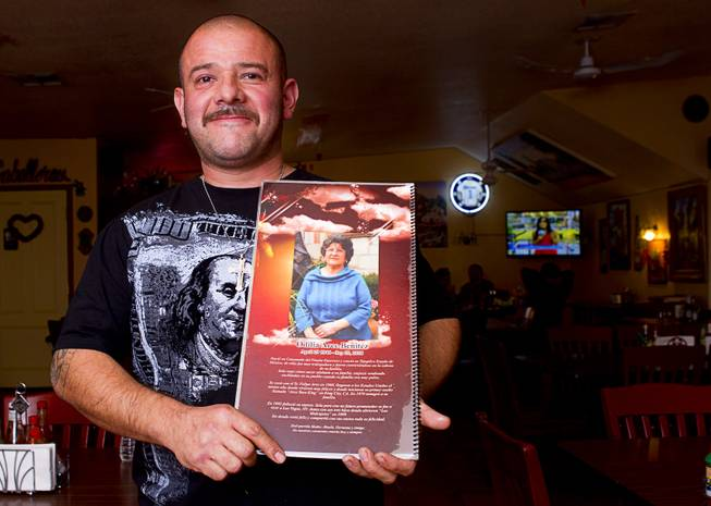 Owner David Arce poses with a menu at Los Molcajetes restaurant, 1553 N. Eastern Ave., Thursday, Feb. 20, 2014.  The back of the menu is dedicated to his mother Odilia Arce Benitez who passed away in 2010. His mother and the family opened the restaurant in 1999.