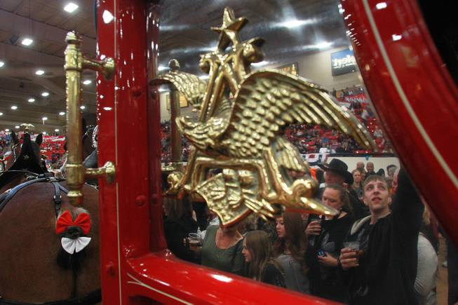 Attendees are reflected in the polished metal of the beer wagon as they get an up close look at the Budweiser Clydesdales during an appearance at the South Point Arena Thursday, Feb. 20, 2014.