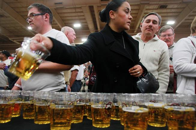 Attendees pick up glasses of free beer during an appearance of the Budweiser Clydesdales at the South Point Arena Thursday, Feb. 20, 2014.