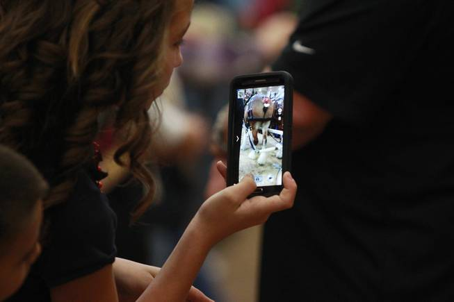 An attendee uses her phono to take a picture during an appearance of the Budweiser Clydesdales at the South Point Arena Thursday, Feb. 20, 2014.