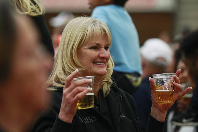 An attendee poses for a photo with her beer during an appearance of the Budweiser Clydesdales at the South Point Arena Thursday, Feb. 20, 2014.