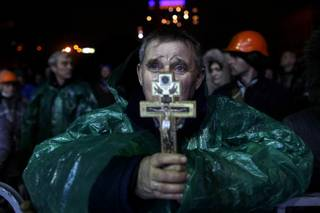 An anti-government protester holds a crucifix as he prays at Independence Square in Kiev, Ukraine, Thursday, Feb. 20, 2014. Ukraine's protest leaders and the president they aim to oust called a truce Wednesday, just hours after the military raised fears of a widespread crackdown with a vow to defeat