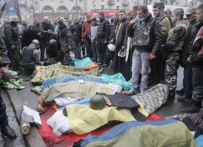 Activists pay respects to protesters who were killed in clashes with police in Kiev's Independence Square, the epicenter of the country's current unrest, Kiev, Ukraine, Thursday, Feb. 20, 2014.