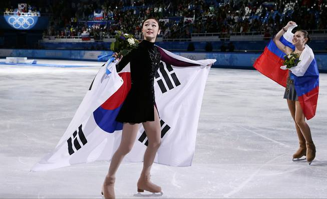 Yuna Kim of South Korea and Adelina Sotnikova of Russia skate on the ice after the flower ceremony for the women's free skate figure skating finals at Iceberg Skating Palace during the 2014 Winter Olympics, Thursday, Feb. 20, 2014, in Sochi, Russia.