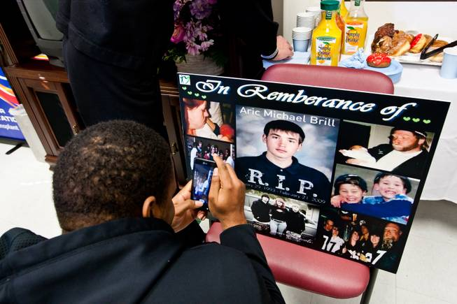 Melvin Gibson takes a photograph of memories of his close friend, Aric, during a ceremony celebrating the life of 16-year-old Aric Michael Brill, who donated six organs following his homicide five years ago, at the UMC Transplant Center Friday, February 21, 2014.