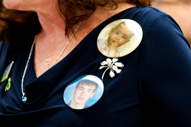 Karen Brill wears photo buttons in memory of her son 16-year-old Aric Michael Brill, who donated six organs following his homicide five years ago, during a ceremony at the UMC Transplant Center Friday, February 21, 2014.