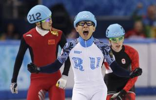 Victor An of Russia, center, reacts as he crosses the finish line ahead of Wu Dajing of China, left, and Charle Cournoyer of Canada in the men's 500m short track speedskating final at the Iceberg Skating Palace during the 2014 Winter Olympics, Friday, Feb. 21, 2014, in Sochi, Russia.