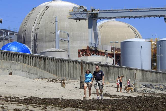 Beach-goers walk on the sand near the San Onofre nuclear power plant in San Clemente, Calif., June 30, 2011. The facility has been closed since 2012.
