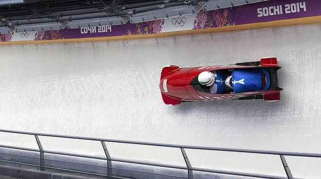 An Italian bobsled brakeman has his head down as he slides down the track at the Sanki Sliding Center during the 2014 Winter Olympics in Krasnaya Polyana, Russia, Feb. 13, 2014.