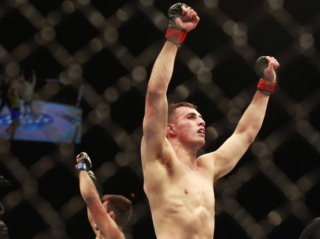 Rory MacDonald raises his arms in victory after defeating Demian Maia at UFC 170 Saturday, Feb. 22, 2014 at the Mandalay Bay Events Center.