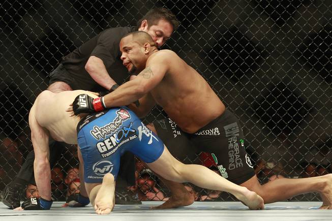 Daniel Cormier gives Patrick Cummins a final shove as referee Mario Yamasaki ends their fight at UFC 170 Saturday, Feb. 22, 2014 at the Mandalay Bay Events Center. Cormier won by TKO in the first round.