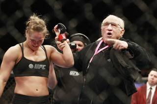 Martial arts legend, coach and friend Gene LaBell raises Ronda Rousey's arm after her first round TKO of Sara McMann in their fight at UFC 170 Saturday, Feb. 22, 2014 at the Mandalay Bay Events Center.