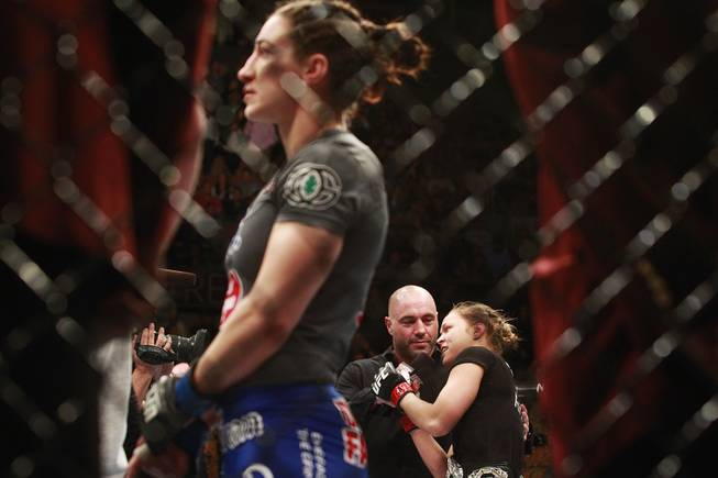 Ronda Rousey talks with Joe Rogan as Sara McMann watches a replay of their fight at UFC 170 Saturday, Feb. 22, 2014 at the Mandalay Bay Events Center. Rousey won by TKO in the first round with a knee to the McMann's liver.