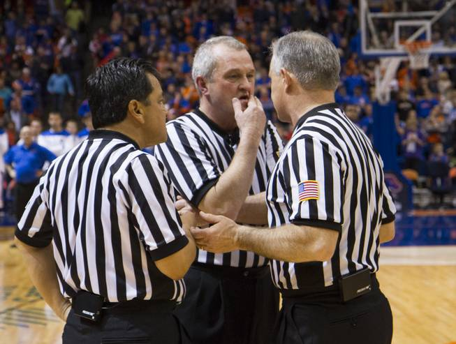 The referees confer during UNLV's 91-90 overtime loss to Boise State at Taco Bell Arena in Boise on Saturday, Feb. 22, 2014.