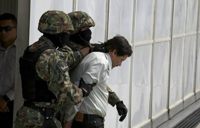 "Joaquin ""El Chapo"" Guzman is escorted to a helicopter in handcuffs by Mexican navy marines at a navy hangar in Mexico City, Saturday, Feb. 22, 2014. A senior U.S. law enforcement official said Saturday that Guzman, the head of Mexico's Sinaloa Cartel, was captured alive overnight in the beach resort town of Mazatlan."
