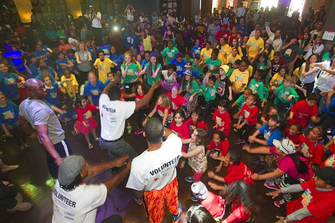 Volunteers lead children in warm-ups during the second annual Dance Against Obesity Camp at the Marquee nightclub in the Cosmopolitan Las Vegas Sunday, Feb. 23, 2014. The free dance clinic was sponsored by TAO Cares and the Jump for Joy Foundation. While the children learned dance moves, parents participated in nutritional seminars.