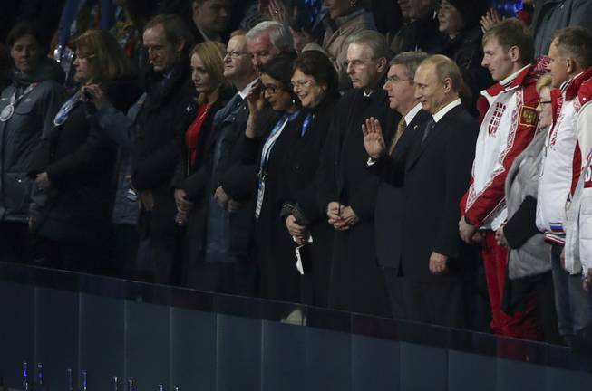 Vladimir Putin, president of Russia, waves as he is introduced during the closing ceremony for the 2014 Winter Olympics at Fisht Olympic Stadium in Sochi, Russia, Feb. 23, 2014. Left of Putin is Thomas Bach, president of the International Olympic Committee, and right of Putin is Russian bobsled gold medalist Alexander Zubkov. (Doug Mills/The New York Times)