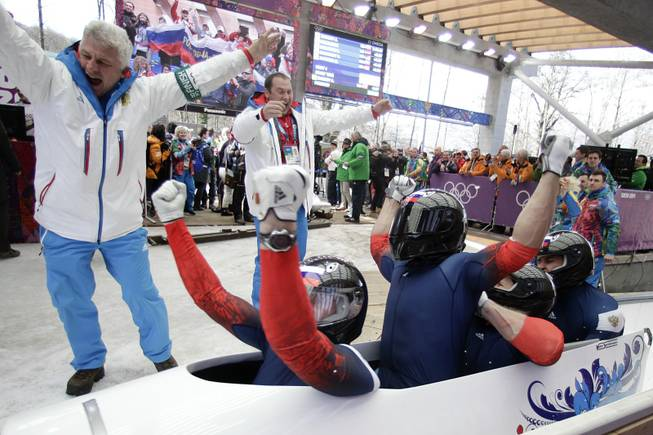 The team from Russia RUS-1, with Alexander Zubkov, Alexey Negodaylo, Dmitry Trunenkov, and Alexey Voevoda, celebrate after they won the gold medal during the men's four-man bobsled competition final at the 2014 Winter Olympics, Sunday, Feb. 23, 2014, in Krasnaya Polyana, Russia.