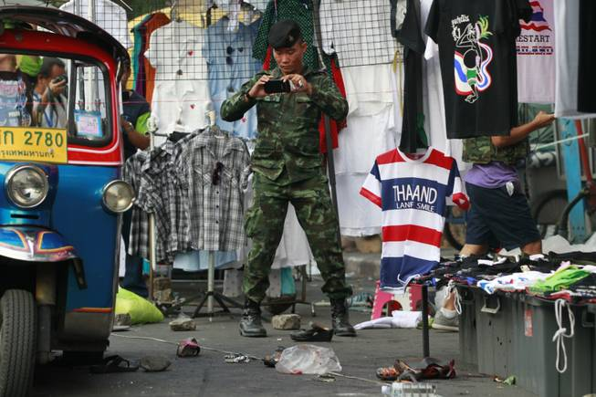 A soldier photographs the scene of an explosion littered with blood and small pairs of shoes at a main protest site in Bangkok, Thailand, Sunday, Feb. 23, 2014. More than a dozen people were hurt Sunday by a small explosion at an anti-government protest in Bangkok, less than a day after a bloodier attack in an eastern province killed one child and left about three dozen people wounded.