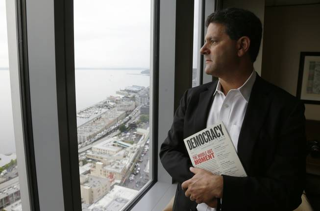 "In this Aug. 2, 2013 file photo, venture capitalist Nick Hanauer stands by the window of his office in downtown Seattle. He holds a copy of ""Democracy: A Journal of Ideas,"" which includes an article he co-authored promoting an economy driven by a strong middle class."