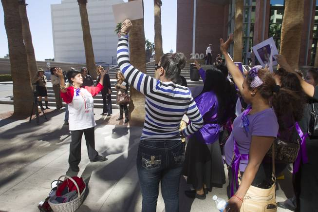 Community activist Rosemary Flores, left, leads people in chants during a rally to increase awareness of machete attack victim Maria Gomez outside Clark County Regional Justice Center Monday, Feb. 24, 2014. Armando Vergara-Martinez is accused in the attack.