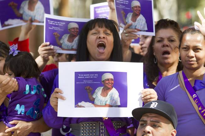 Rebeca Ferreira, center, director of Safe Faith United, holds a photo of machete attack victim Maria Gomez during a rally outside Clark County Regional Justice Center Monday, Feb. 24, 2014. Armando Vergara-Martinez is accused in the 2012 attack.
