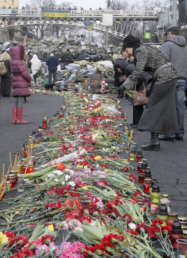 People lays down flowers at one of the streets leading to Independence Square, Kiev, the epicenter of the country's recent unrest, on a mourning day Monday, Feb. 24, 2014.