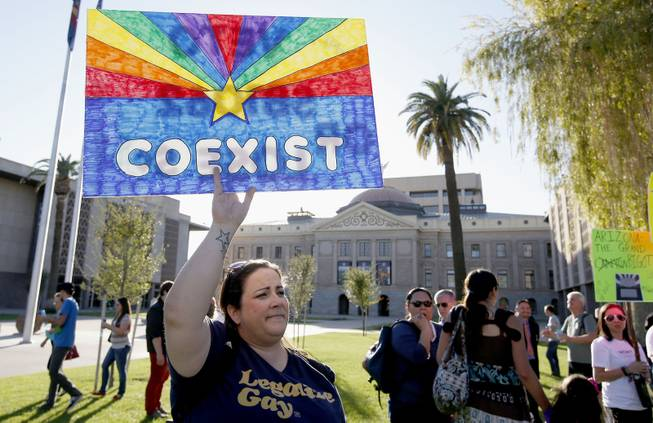 Jo Beaudry holds up a sign as she joins nearly 250 gay rights supporters protesting SB1062 at the Arizona Capitol, Friday, Feb. 21, 2014, in Phoenix.