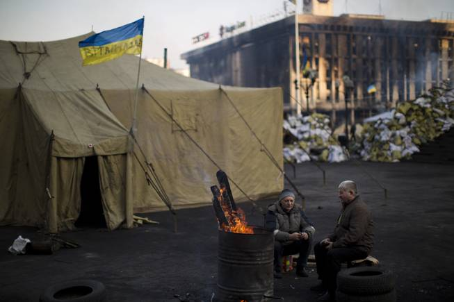 Opposition supporters warm themselves around a fire in Kiev's Independence Square, the epicenter of the country's current unrest, Ukraine, Monday, Feb. 24, 2014.