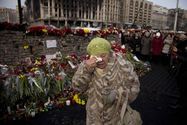 A woman cries near a memorial for the people killed in clashes with the police at Independence Square in Kiev, Ukraine, Monday, Feb. 24, 2014.