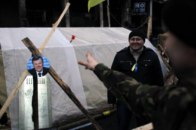 A portrait of Ukraine's President Viktor Yanukovych is used for a game of darts at Independence Square in Kiev, Ukraine, Monday, Feb. 24, 2014.