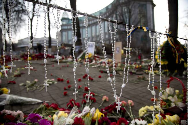 Rosary beads hang on a barricade in Kiev's Independence Square, the epicenter of the country's current unrest, Ukraine, Monday, Feb. 24, 2014.
