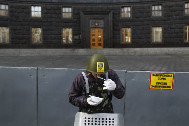 A protester eats as he stands guard in front of the Ukrainian government building in Kiev, Ukraine, Monday, Feb. 24, 2014.