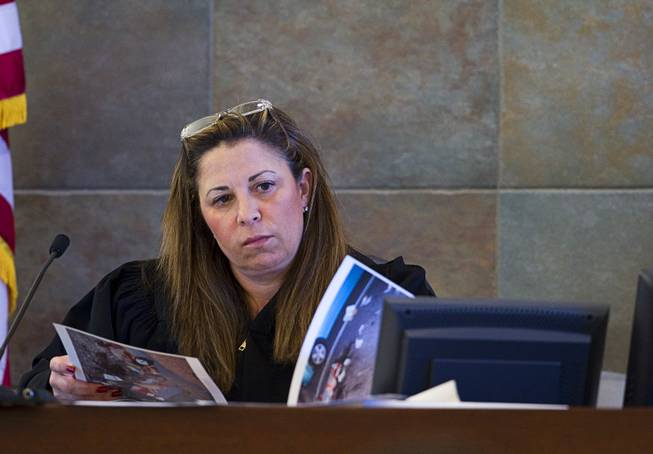 Judge Abbi Silver looks over crime scene photos during a trial for Armando Vergara-Martinez at the Clark County Regional Justice Center Tuesday, Feb. 25, 2014. Martinez is accused of attacking Maria Gomez with a machete in the parking lot of a North Las Vegas convenience store in 2012.