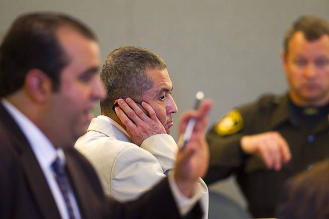 Armando Vergara-Martinez, center, listens to a Spanish interpreter through an earphone during his trial at the Clark County Regional Justice Center Tuesday, Feb. 25, 2014. Martinez is accused of attacking Maria Gomez with a machete in the parking lot of a North Las Vegas convenience store in 2012.