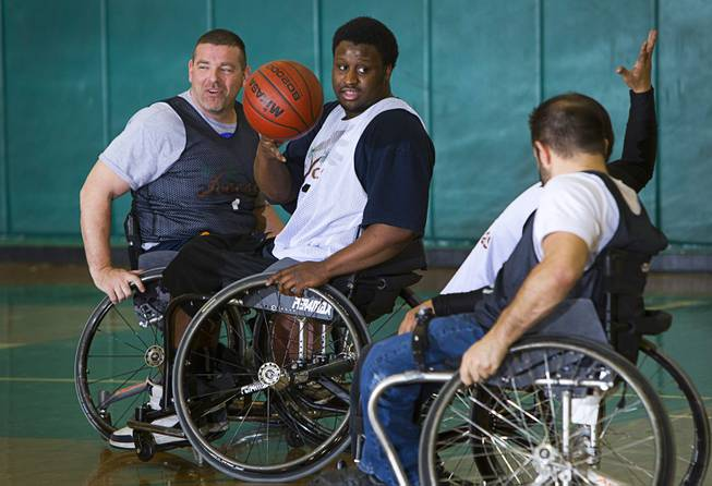 Marc Fenn, left, Timothy Oliver, center, and other wheelchair basketball team members practice at Rancho High School Tuesday, Feb. 25, 2014. The team is practicing for a scrimmage against a Wounded Warriors team at Nellis Air Force Base on Thursday.