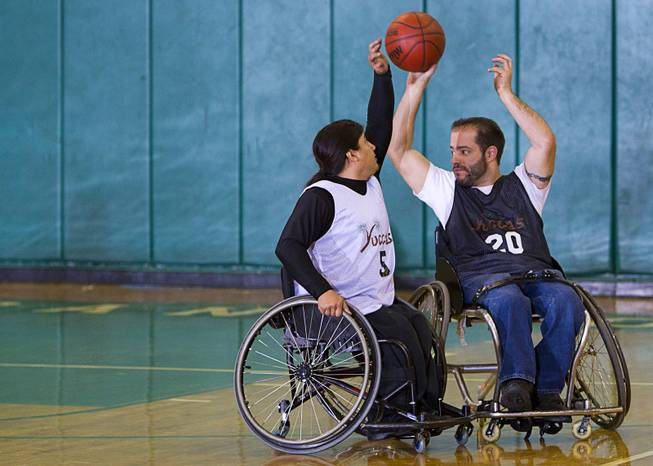 Steven Morales, left, defends against teammate Mike Humel during wheelchair basketball practice at Rancho High School Tuesday, Feb. 25, 2014. The team is practicing for a scrimmage against a Wounded Warriors team at Nellis Air Force Base on Thursday.