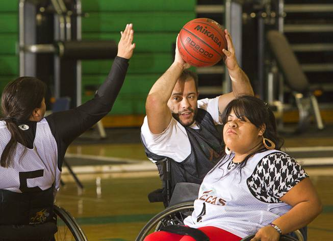 Mike Humel, center, practices with Steven Morales, left, and Cinthya Huendo at Rancho High School Tuesday, Feb. 25, 2014. The wheelchair basketball team is practicing for a scrimmage against a Wounded Warriors team at Nellis Air Force Base on Thursday.